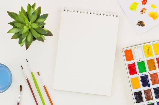 Caderno de vista superior rodeado por elementos de pintura Foto gratuita