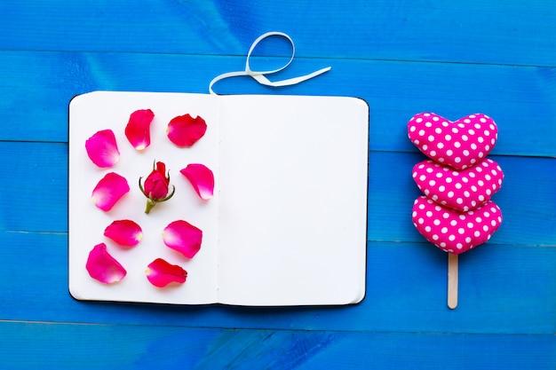 Caderno do diário com corações cor-de-rosa e do valentim no fundo de madeira azul. Foto Premium