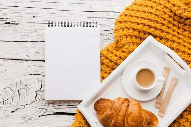 Caderno e bandeja com café da manhã Foto gratuita