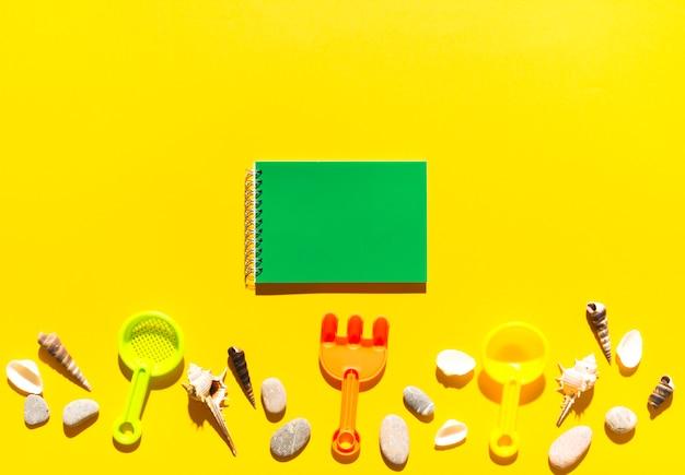Caderno e brinquedos de praia Foto gratuita
