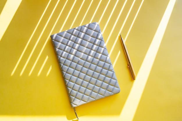 Caderno e caneta sobre um fundo amarelo Foto Premium
