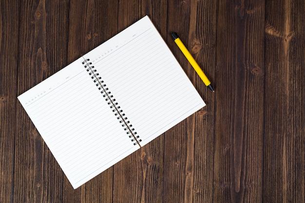 Caderno e papel branco vazio com caneta na madeira Foto Premium