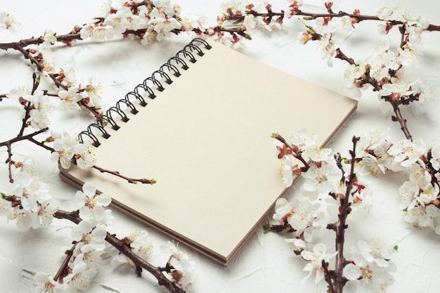 Caderno e um raminho de flores de cerejeira em pedra Foto Premium
