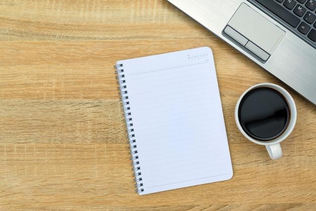 Caderno e xícara de café na mesa de trabalho Foto Premium