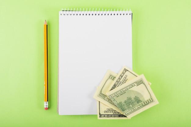 Caderno em branco com dinheiro na mesa Foto gratuita