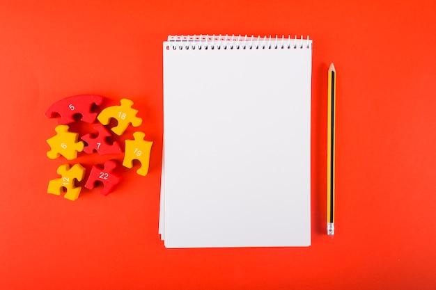 Caderno em branco com quebra-cabeças na mesa Foto gratuita