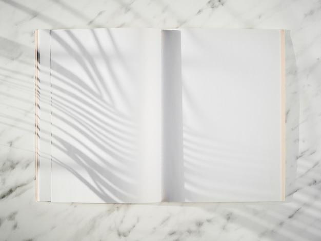 Caderno em branco com vista superior de sombras Foto gratuita