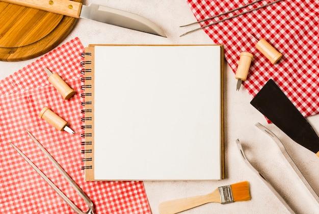Caderno em branco e ferramentas de grelhar Foto gratuita