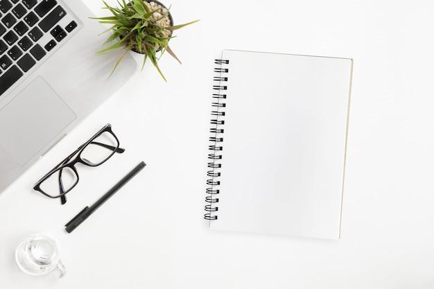 Caderno em branco está no topo da mesa de escritório branco. vista superior, lay plana. Foto Premium