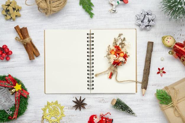 Caderno em branco na madeira branca com enfeites de natal. Foto Premium