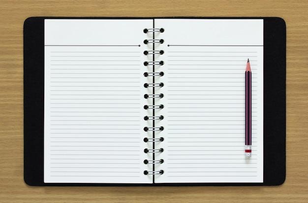 Caderno em espiral em branco e lápis em fundo de madeira Foto gratuita