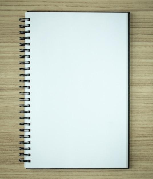 Caderno em espiral em branco no fundo de madeira Foto Premium