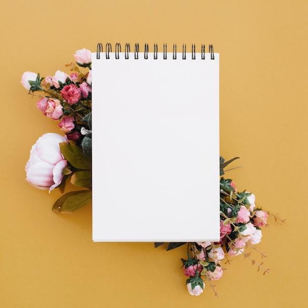 Caderno em um fundo dourado bonito com flores bonitas Foto gratuita