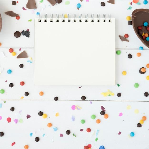 Caderno entre doces, ovo de chocolate e confetes Foto gratuita