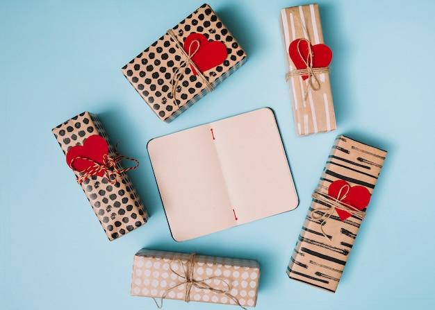 Caderno entre presentes em papéis doçura com corações decorativos Foto gratuita