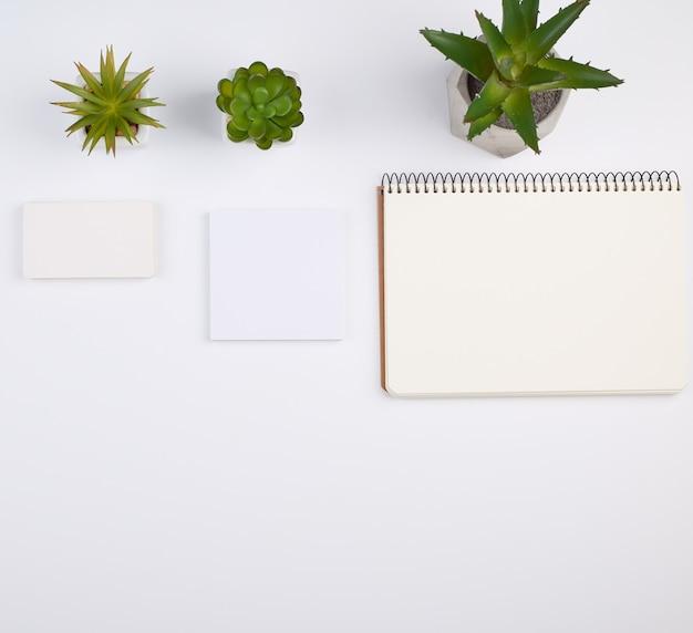 Caderno espiral aberto com folhas vazias, vasos com plantas de interior verdes sobre uma mesa branca Foto Premium