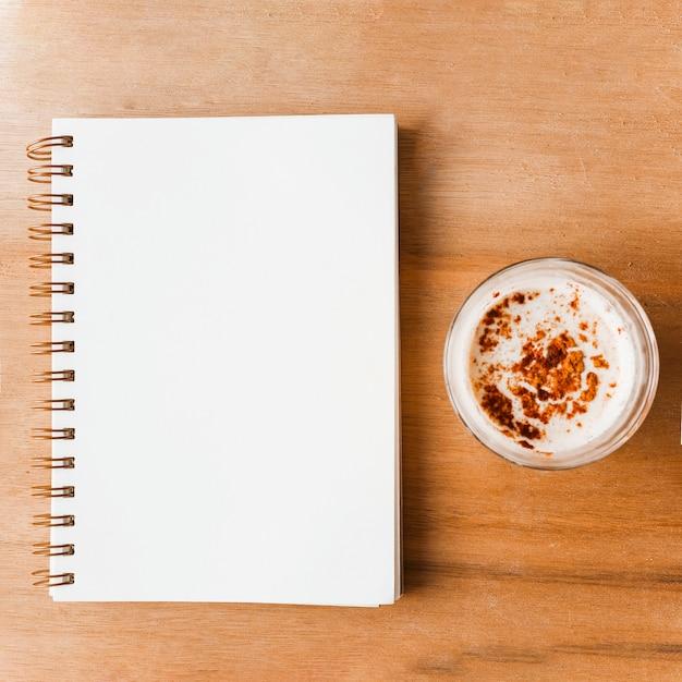 Caderno espiral branco fechado e copo de café com cacau em pó Foto gratuita