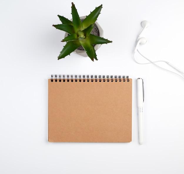 Caderno espiral com folhas vazias, caneta e plantas verdes Foto Premium