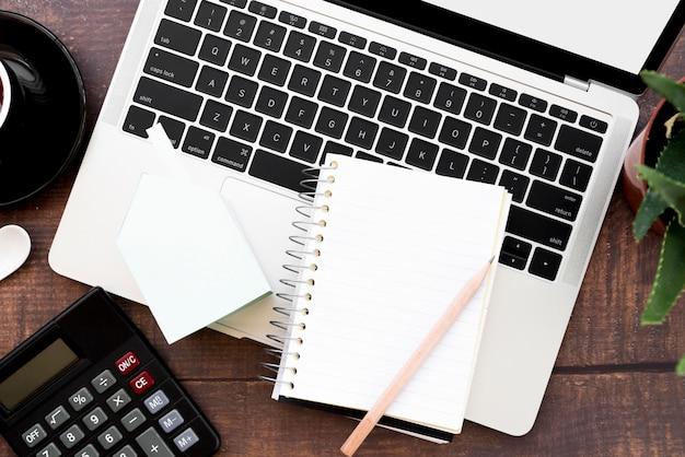 Caderno espiral em branco com lápis sobre um laptop aberto na mesa de madeira Foto gratuita