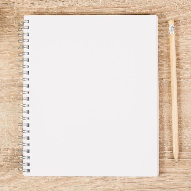 Caderno espiral em branco e lápis de madeira na mesa de madeira Foto Premium