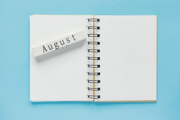 Caderno espiral limpo para anotações e mensagens e barra de calendário de madeira de agosto. configuração mínima de negócios Foto Premium
