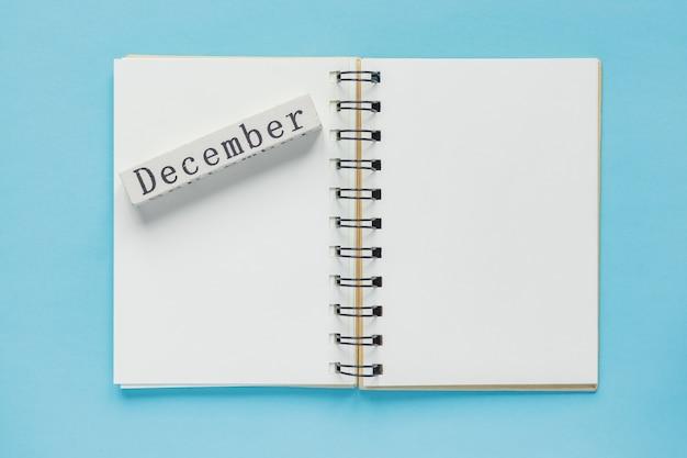 Caderno espiral limpo para anotações e mensagens e barra de calendário de madeira de dezembro. configuração mínima de negócios Foto Premium
