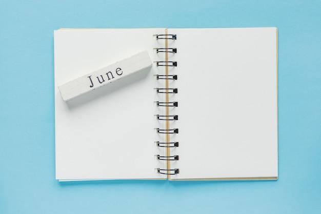 Caderno espiral limpo para anotações e mensagens e barra de calendário de madeira de junho Foto Premium