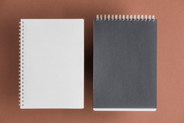 Caderno espiral preto e branco em fundo colorido Foto gratuita