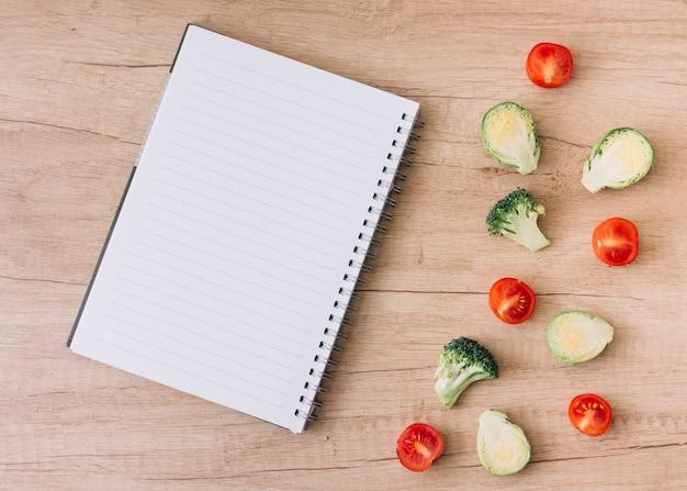 Caderno espiral vazio com couves-de-bruxelas divididas ao meio; tomates e brócolis na mesa de madeira Foto gratuita