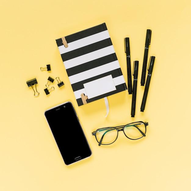 Caderno fechado com canetas de feltro; clipes de papel de bulldog; óculos e celular em fundo amarelo Foto gratuita
