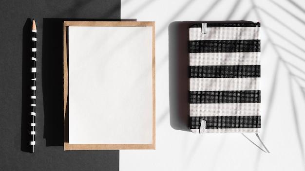 Caderno listrado preto e branco e manta branca com um lápis listrado preto e branco em um fundo preto e branco com uma sombra de folha Foto gratuita