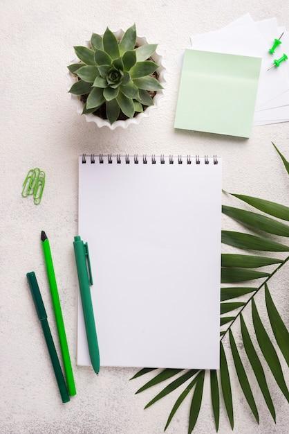 Caderno na mesa com canetas e folhas Foto gratuita