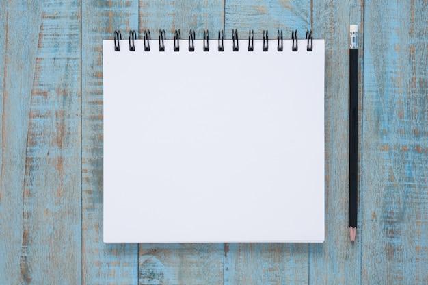 Caderno na mesa de madeira azul Foto gratuita