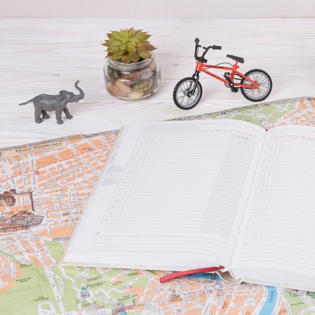 Caderno no mapa perto de animal de brinquedo e bicicleta Foto gratuita