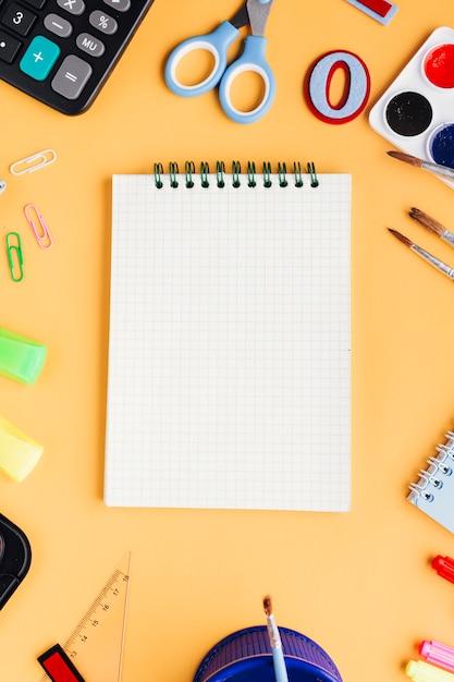 Caderno novo branco rodeado por artigos de papelaria em fundo bege Foto gratuita
