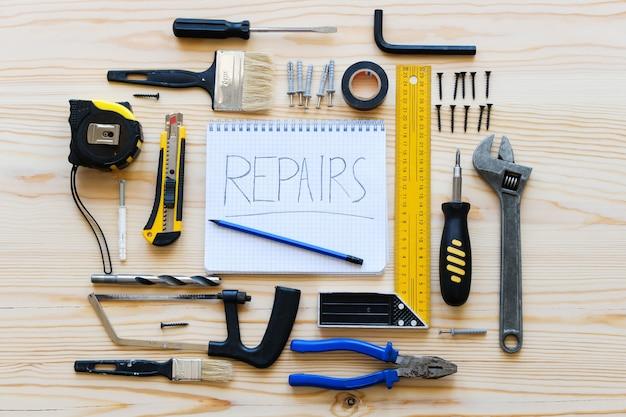 Caderno para registros e ferramentas da construção para construir uma renovação da casa ou do apartamento, em uma tabela de madeira. o local de trabalho do capataz. o tema da casa e reparação profissional, construção. Foto Premium