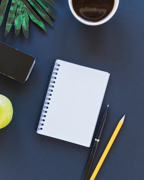 Caderno perto de xícara de café e artigos de papelaria na mesa com maçã e palmeiras Foto gratuita