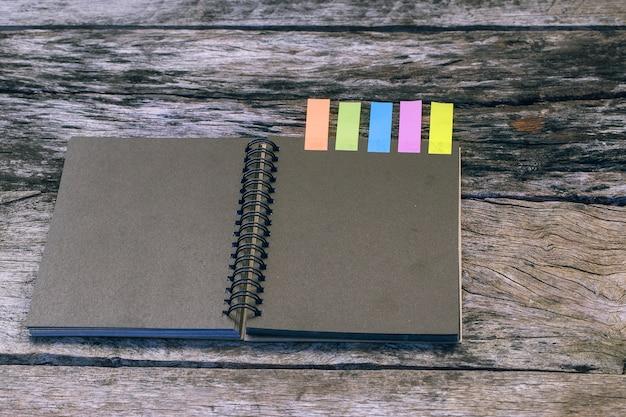 Caderno preto com aba de nota de cores na mesa de madeira. conceito de estudo de caso Foto Premium