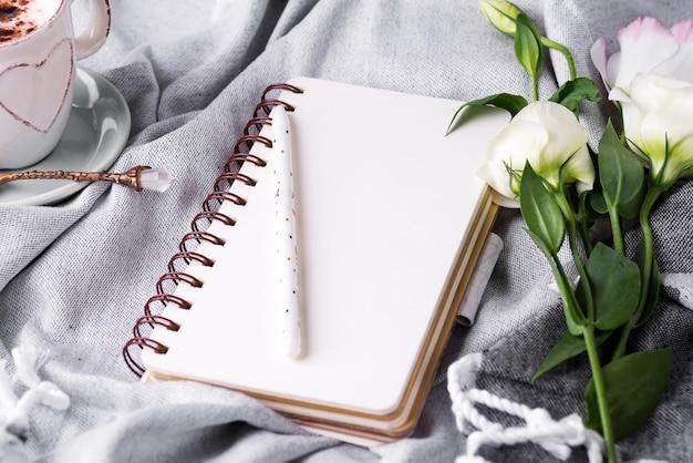 Caderno vazio aberto e buquê de eustoma de flores sobre fundo cobertor. lindo cartão em estilo vintage. postura plana. Foto Premium