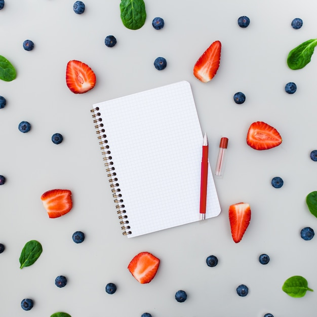 Caderno vazio com morangos e mirtilos em fundo cinza Foto gratuita