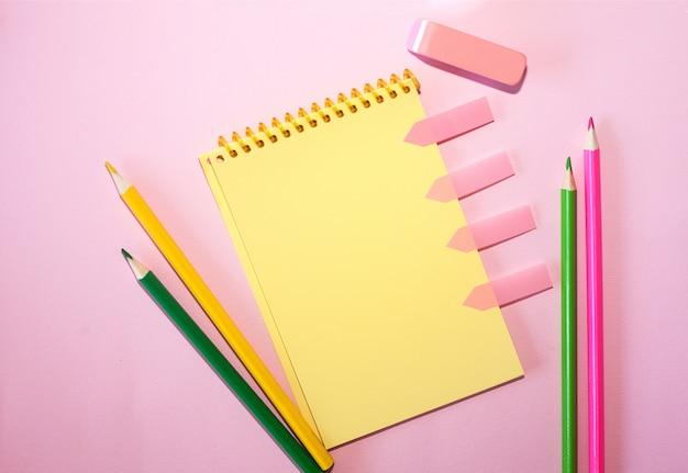 Caderno vazio com os lápis coloridos contra o fundo pastel cor-de-rosa. Foto Premium