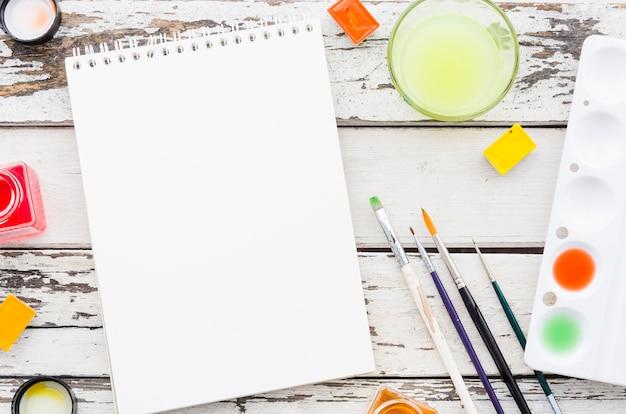 Caderno vazio de vista superior com material de pintura Foto gratuita