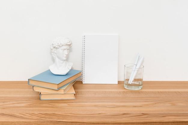 Caderno vazio na mesa de madeira com livros e uma pequena escultura de gesso de david Foto Premium