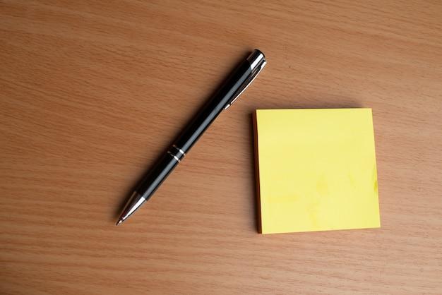 Cadernos amarelos com caneta preta sobre a mesa de madeira Foto Premium