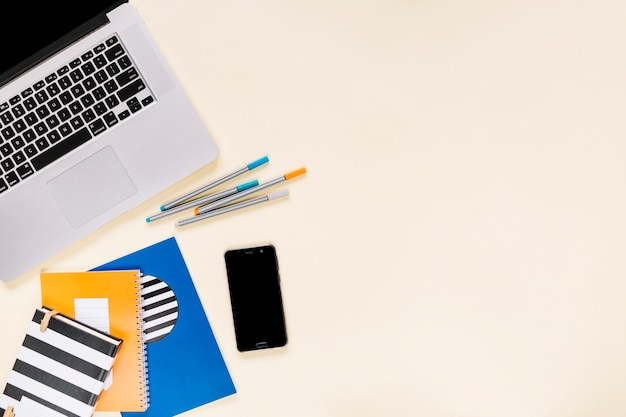 Cadernos coloridos e canetas de feltro com celular e laptop em fundo creme Foto gratuita