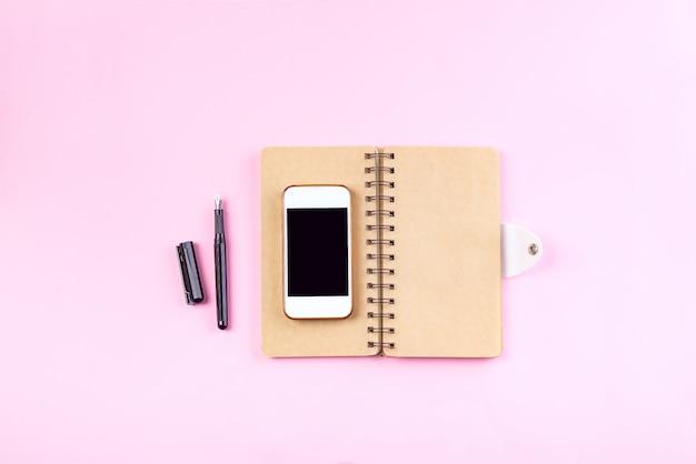 Cadernos de artesanato, caneta e telefone inteligente em um fundo rosa pastel Foto Premium