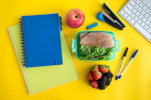 Cadernos, lancheira e papelaria na mesa Foto gratuita