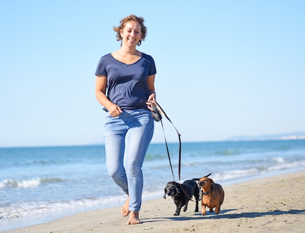 Cães e mulher na praia Foto Premium