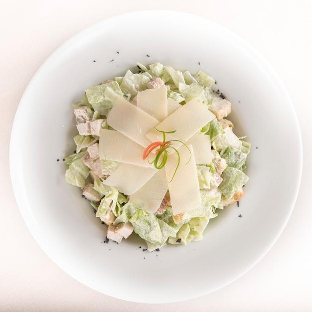 Caeser salad com filé de frango, chapa branca, fundo marrom Foto Premium