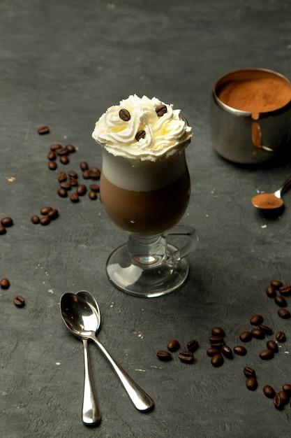 Café aromático em um copo de vidro com chantilly Foto gratuita
